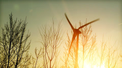 Silhouette of wind turbine at sunrise long shot - orange sky and lens flare. - stock footage