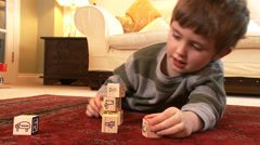 A young boy no older than 4 years old stacks play bricks until they collapse. - stock footage