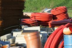 Storage of building material and red tubes in a construction site Stock Photos