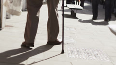 Low angle view of elderly person walking through uk commercial area - stock footage