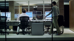 Evening planning meeting. Office business people with computers and plans in - stock footage