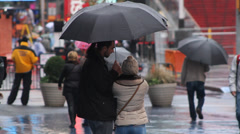 Times Square, fall, man and woman Facetime under umbrella Stock Footage