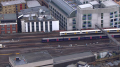Aerial view of passenger trains passing at a London city station Stock Footage