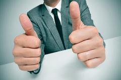 Man in suit giving a thumbs up signal Stock Photos