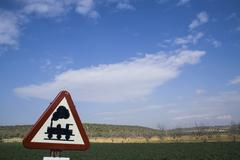 warning sign worn of level crossing without barriers, blue sky with clouds - stock photo