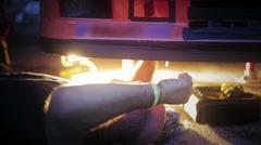 Passionate man repairing car at night Stock Footage