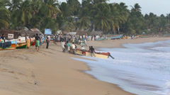 Fishermen drag a fishing boat up the beach Stock Footage