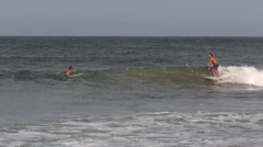 Surfer riding wave on tropical surfing beach Stock Footage