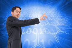 Stock Illustration of Composite image of serious asian businessman pointing
