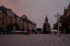Timisoara center square at sunset with people in street and long exposure Stock Photos