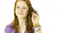 Teenage girl isolated on white listening to music Stock Footage