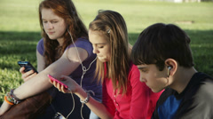 Stock Video Footage of teenagers outdoor looking at their smart phones