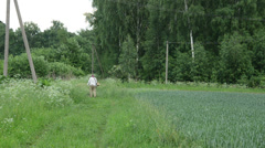 Man with trimmer cuts grass on rural road after rain Stock Footage