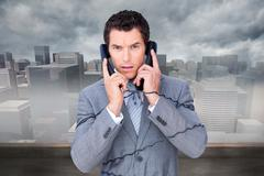Stock Illustration of Composite image of angry businessman tangle up in phone wires