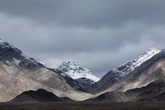 Snow covered mountains and an ominous sky, in Death Valley national park. Stock Photos