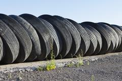 A row of discarded automobile tires stacked up near Wendover, in Utah. Stock Photos