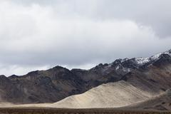 Snow covered mountains and an ominous sky, in Death Valley national park. - stock photo