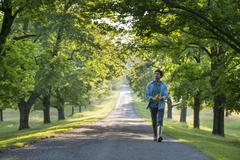 A man walking down a tree lined path. - stock photo