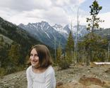 Stock Photo of A young girl sitting at a lookout point, with a view over the mountains