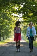 Two women walking down a path lined with trees. - stock photo