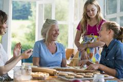 Farmhouse in the country. Four generations of women in a family baking together. - stock photo