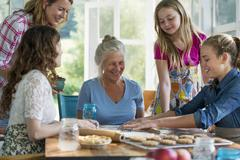 Farmhouse in the country. Four generations of women in a family baking together. Stock Photos