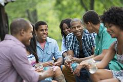 A group of men and women outdoors enjoying themselves. Stock Photos