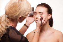 Beautician applying eye makeup Stock Photos