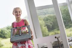 A young girl in a kitchen carrying a terrarium containing small plants. Stock Photos
