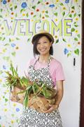 A young Asian woman by the Welcome sign with a large basket of vegetables - stock photo