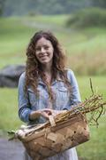 A young woman carrying a basket of freshly harvested garlic and vegetables. Stock Photos