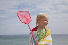 A young girl with a beach towel around her shoulders, carrying a fishing net. Stock Photos