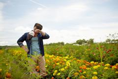 A farmer working in his fields. A yellow and orange organic flower crop. - stock photo
