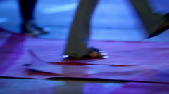 Person in sandals is unfolding the red carpet on concrete Stock Footage