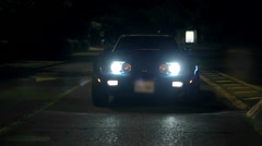 Corvette is slowly approaching the camera with the headlights light up Stock Footage