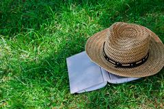 Book and straw hat on grass Stock Photos