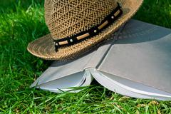book and straw hat on grass - stock photo