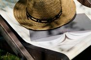 Stock Photo of book and straw hat on deckchair