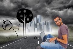 Composite kuva mies silmälaseja istuu lattialla käyttää kannettavaa tietokonetta Piirros
