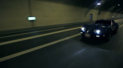 Diagonal shot of Corvette's drive by in a tunnel Stock Footage