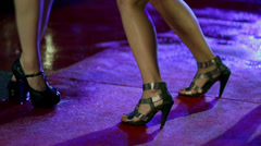 Shot of women legs making dancing moves on wet red carpet - stock footage