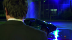 Stock Video Footage of Shot of a man standing in front of blue Corvette with spurting hydrant