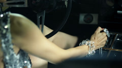Woman covered in glittering jewellery changes the gear while driving Corvette Stock Footage