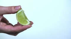 Squeezing a piece of lime with squirting juices Stock Footage