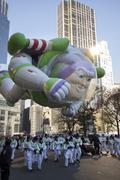 Buzz lightyear balloon flying through city in 2013 Macy's Parade Stock Photos