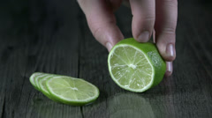 Making a slice of lime on wooden-like tablecloth Stock Footage