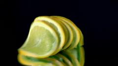 Sliced lemon falls down on black  background in slow motion Stock Footage