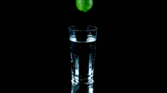 Whole lime falls into glass of water and spurts water around the table - stock footage