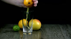 Juice from squeezing an orange is flowing info a cup Stock Footage