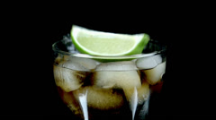 Pieces of lime fall into coke with ice cubes in slow motion Stock Footage